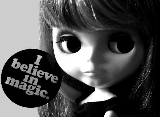 "Black & white photo of Blythe doll holding a button that says ""I believe in magic."""